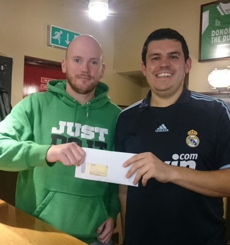 John being presented with his winnings in club sponsors Donohoes Bar by committee member Nordine Chigara